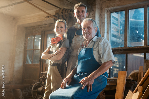 Generations of carpenters in their family business workshop - 360945505