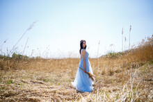 Woman In A Blue Long Dress In The Reeds. Fashion Portrait With Dried Flowers