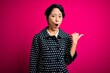 Leinwandbild Motiv Young beautiful asian girl wearing casual jacket standing over isolated pink background Surprised pointing with hand finger to the side, open mouth amazed expression.
