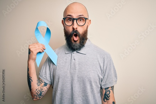 Fényképezés Handsome bald man with beard and tattoos holding blue cancer ribbon over isolate