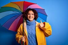 Middle Age Curly Hair Woman Wearing Rain Coat Holding Colorful Umbrella Over Blue Background With Surprise Face Pointing Finger To Himself