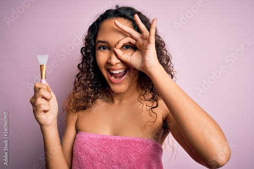 Foto Beautiful woman with curly hair wearing shower towel holding spatula over pink b