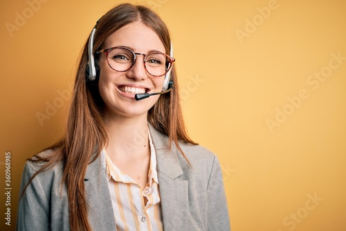Papel de parede Young redhead call center agent woman overworked wearing glasses using headset with a happy and cool smile on face