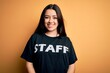Young brunette worker woman wearing staff t-shirt as uniform over yellow isolated background with a happy face standing and smiling with a confident smile showing teeth