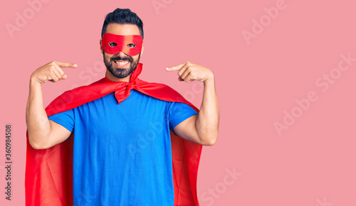 Fotografering Young hispanic man wearing super hero costume looking confident with smile on face, pointing oneself with fingers proud and happy