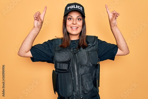 Fotografie, Obraz Young beautiful brunette policewoman wearing police uniform bulletproof and cap smiling amazed and surprised and pointing up with fingers and raised arms