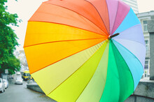 Large Round Multicolored Rainbow Umbrella With Drops On Wet Rainy Street On The Background