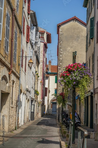 Vertical shot of a narrow street with tall houses on both sides in Bayonne, France