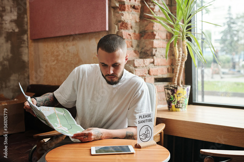 Photo Serious pensive bearded tourist sitting at small table with Please sanitize sign