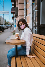 Woman In A Medical Mask Drinks...