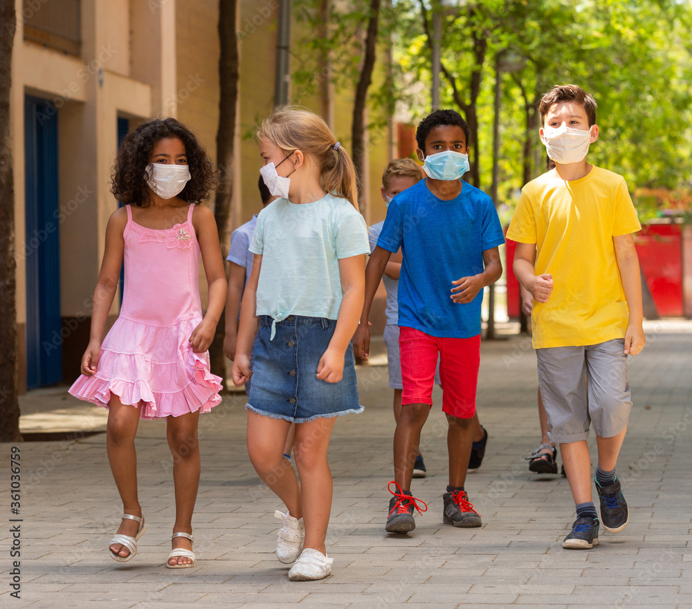 Fototapeta Group of positive children in masks walking together