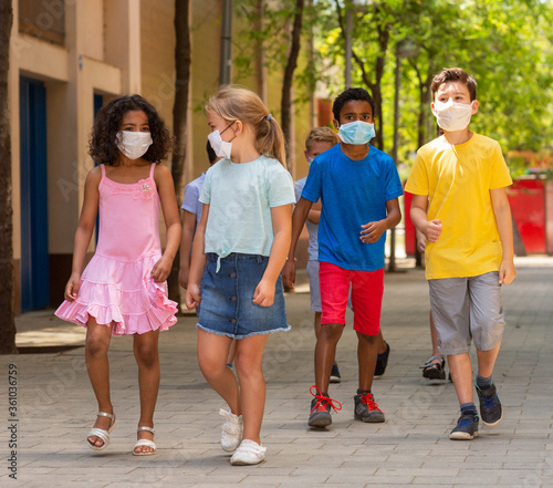 Obraz Group of positive children in masks walking together - fototapety do salonu