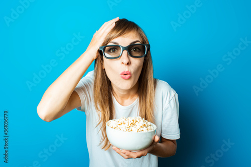 Young beautiful woman in a white T-shirt with a surprised face and glasses for 3D and iMAX holds a plate with popcorn on a blue background Wallpaper Mural