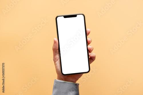 Obraz Smartphone mockup. Close up hand holding black phone white screen on yellow background. Mobile phone frameless design concept. - fototapety do salonu