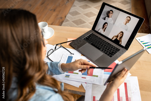 Young attractive business lady have video discussion with partners in the office Wallpaper Mural