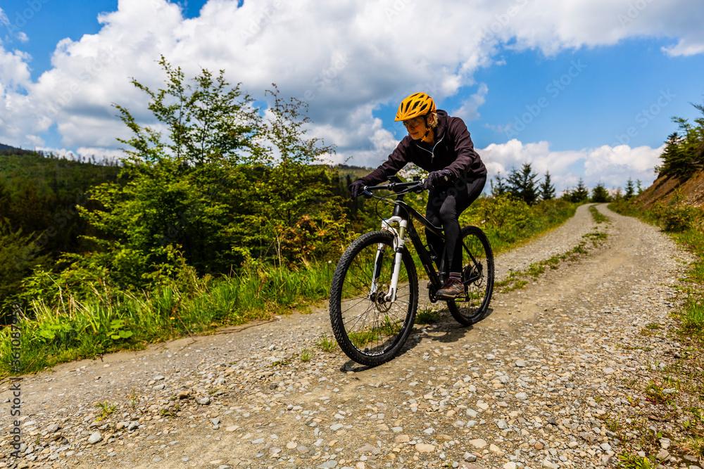 Fototapeta Cycling woman on mtb bike on gravel mountain road, Beskidy, Poland.