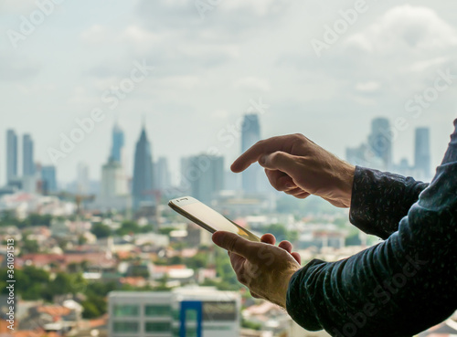Vászonkép A man uses a phone against the backdrop of a panorama of a metropolis