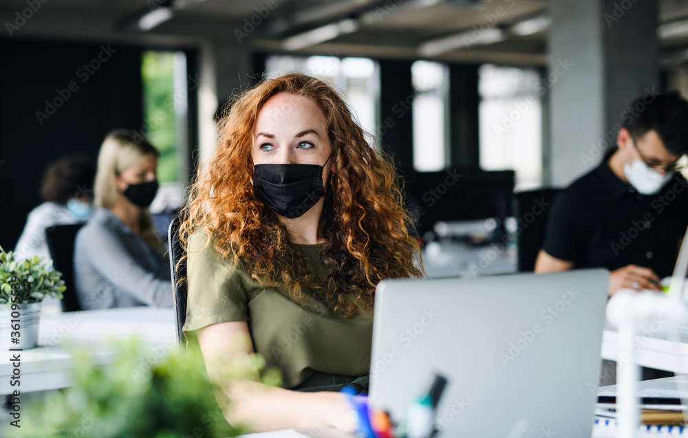 Fototapeta Young woman with face mask back at work in office after lockdown.