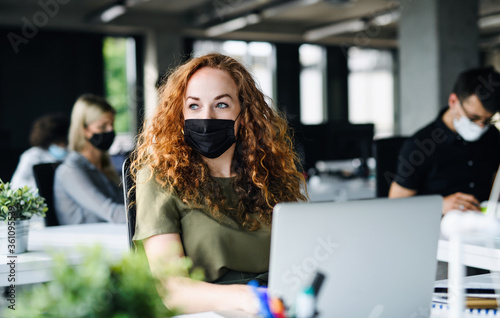 Young woman with face mask back at work in office after lockdown. - 361095539