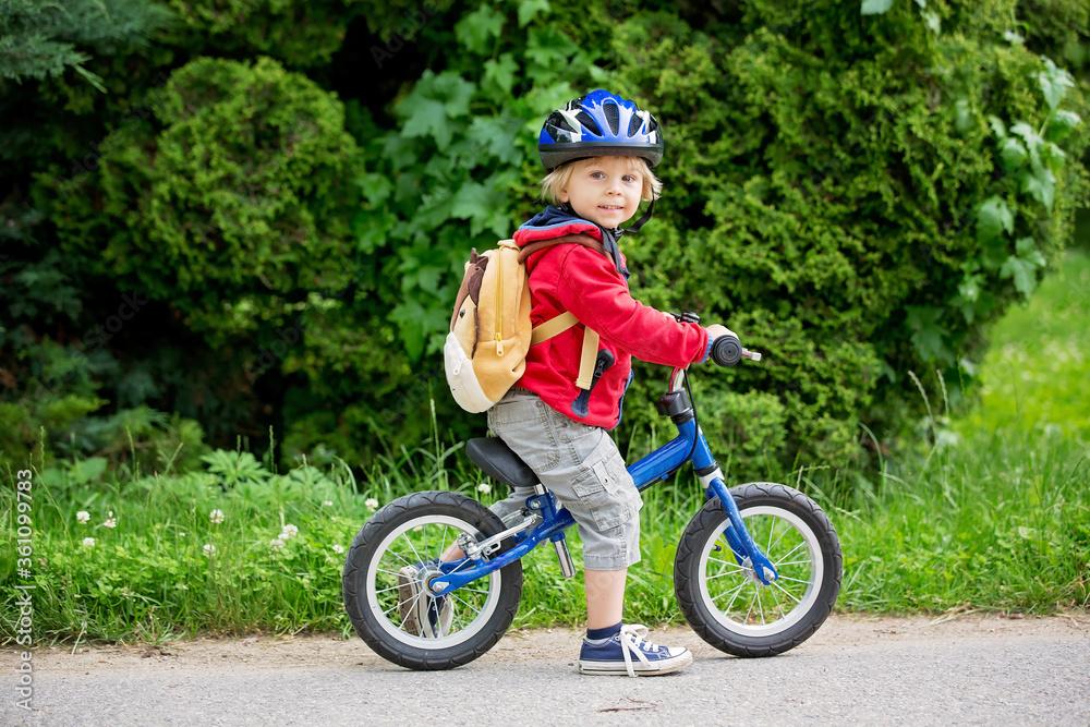 Fototapeta Cute toddler boy with blue helmet, riding balance bike on the street