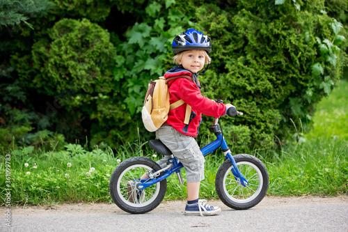 Fototapeta Cute toddler boy with blue helmet, riding balance bike on the street obraz