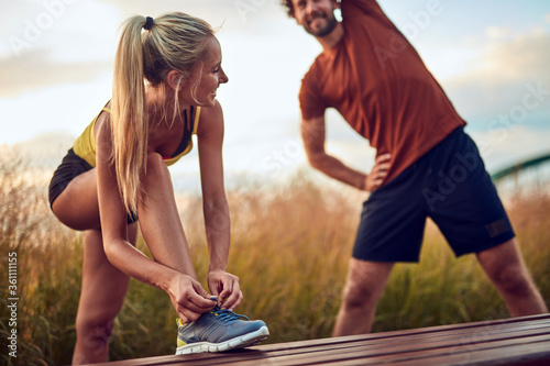 Fototapeta Young adult sporty couple working out outdoors. obraz