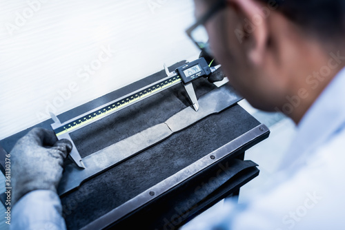 Fotografía Tensile Testing, Engineer using digital vernier to measure the elongation period of the material specimen in the industrial factory laboratory