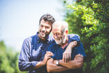 Fototapeta Na ścianę - happy hipster adult son and senior father hugging at home, concept of stay at home with family