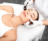 Fototapeta Tulipany - Beautician doing skin treatment using a microneedle derma roller. Woman getting procedure skincare, with mezzo skin roller
