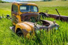 Abandoned Antique Yellow Truck And Tractor In The Tall Grass On A Hillside Near Wymark, SK