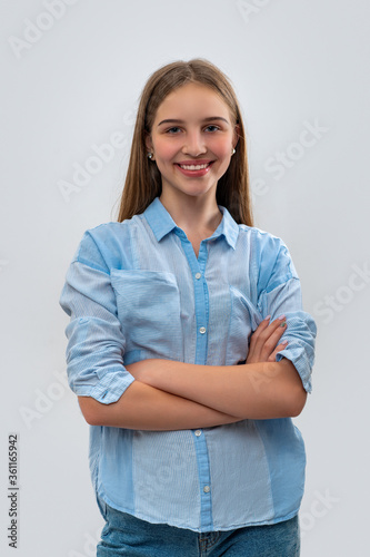 Fotografie, Tablou Studio shot of young smiling girl teenager with cross arms, isolated