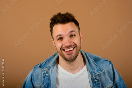 Tablou Canvas Handsome man standing and smiling isolated on light brown studio background