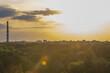 Sunset in summer over the evening industrial city, sun glare and light illumination.