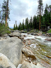 River And Boulders Running Through Forest With Clouds In The Tree-lined Sky