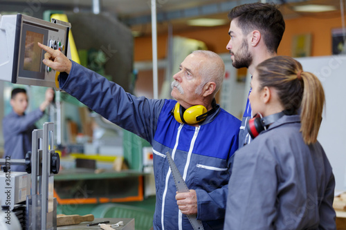 Fototapeta apprentice electrical engineers in cable finishing factory obraz