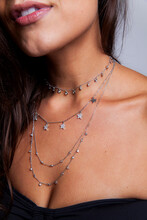 Young Woman Chest Closeup With Necklaces And Rings