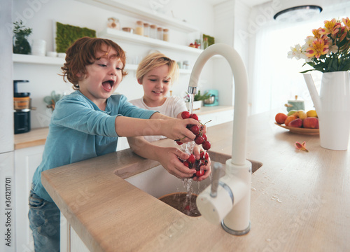 Obraz na plátne happy kids washing cherries under tap water at the kitchen