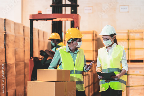 Fototapeta Asian engineers in helmet and face mask hold clipboard in warehouse  obraz