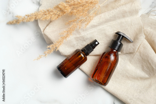 Valokuva Dark amber glass bottles set with beige fabric and dry flowers on marble background