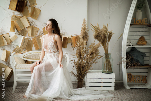 Photo A beautiful boudoir morning of the bride, a pretty girl in a white man's shirt a