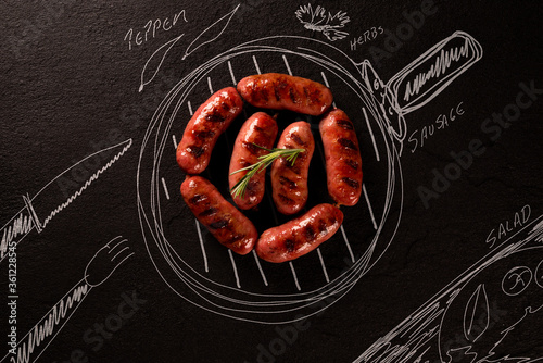 Fotografia Roasted sausage on black chalkboard with painted pan and ingredients