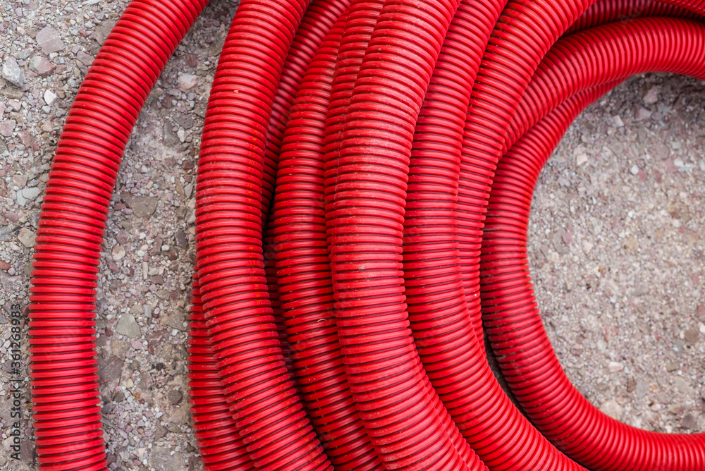 Red plastic tubing for underground cable protection on the street