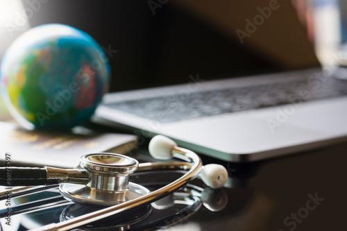 Valokuvatapetti Blurred image of medical stethoscope, passport book, globe and laptop computer