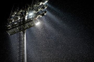 A swarm of mosquitoes and other night insects fly in the light of a stadium reflector near a big river