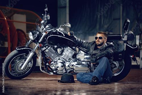 Cool man biker in sunglasses sitting near his motocycle Fototapet
