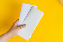 Woman's Hands Are Holding Empty Mock-up Brochure For Writing Letter Above Yellow Background