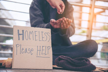 Woman Helping Hands To Homeles...