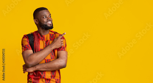 Fotografie, Tablou Happy african man in traditional costume pointing at free space