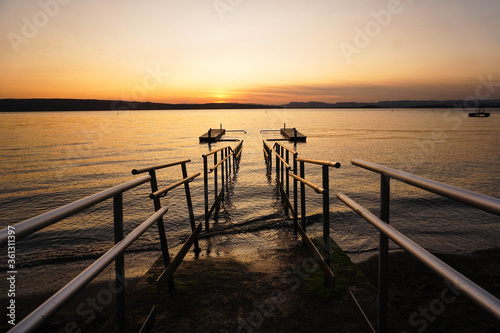 Photo Bridge of a lake with mountains in a sunset