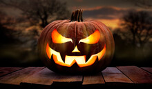One Spooky Halloween Pumpkin, Jack O Lantern, With An Evil Face And Eyes On A Wooden Bench, Table With A Sunset, Night Background.